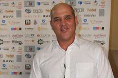 Jorge Mandilego, the CEO of Cuba Emprende poses at the Sponsors banner.